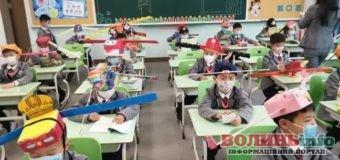 Тримають відстань. У Китаї діти прийшли до школи в метрових капелюхах.